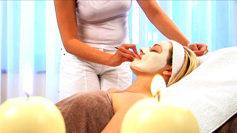 Young blonde girl having facial skin mask applied at... Stock Video Footage