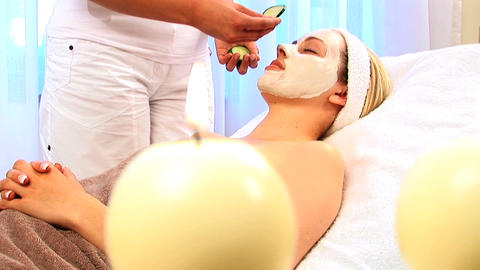 Young blonde girl resting with facial skin mask at beauty... Stock Video Footage