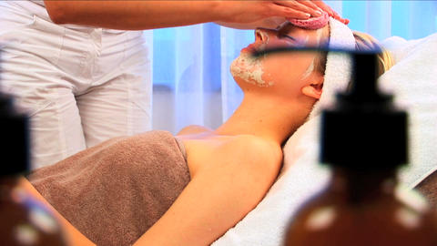 Young blonde girl having facial skin mask removed at... Stock Video Footage