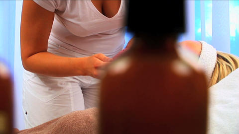 Young blonde girl having facial skin mask removed at beauty spa with lotion bottles in foreground Footage