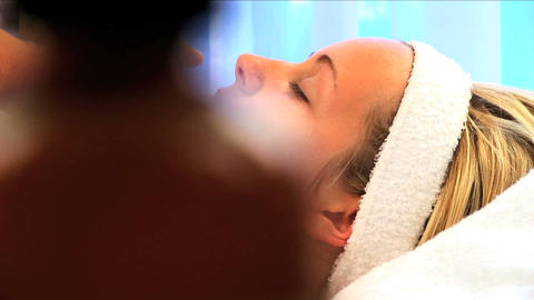 Young blonde girl having facial treatment at beauty spa with lotion bottles in foreground Footage