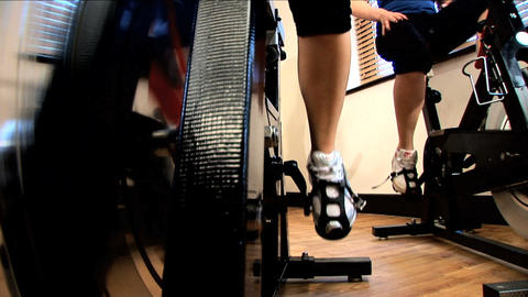 Close-up legs & feet working an exercise machine at a gym Stock Video Footage