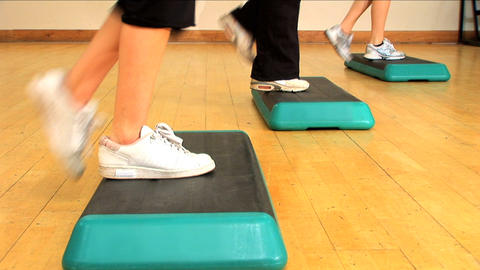 Close-up legs & feet doing step exercises at a gym Footage