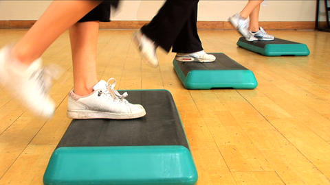Close-up legs & feet doing step exercises at a gym Stock Video Footage