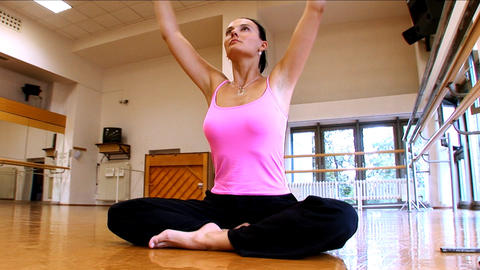 Attractive slim brunette girl practising yoga exercises at a gym Footage