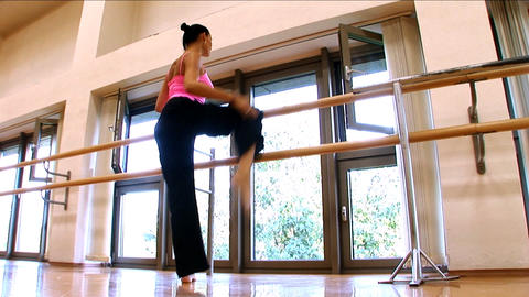 Attractive slim brunette girl practising yoga exercises at a gym Live Action