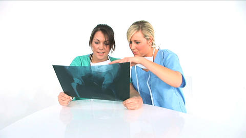 Two young female healthworkers analyzing x-ray exposure Stock Video Footage