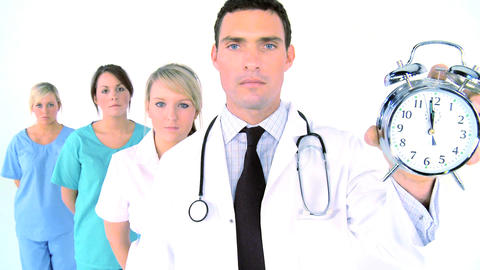 Medical team - doctor holding ringing alarm clock showing... Stock Video Footage