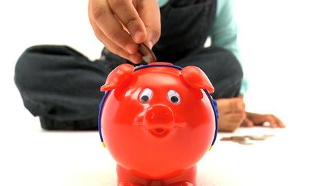 Little girl insert coins into a piggy bank Footage