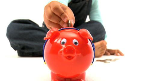 Little girl insert coins into a piggy bank Stock Video Footage