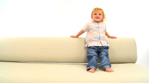 Cute toddler skipping on the sofa isolated on white Footage
