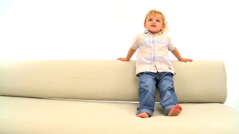 Cute toddler skipping on the sofa isolated on white Stock Video Footage