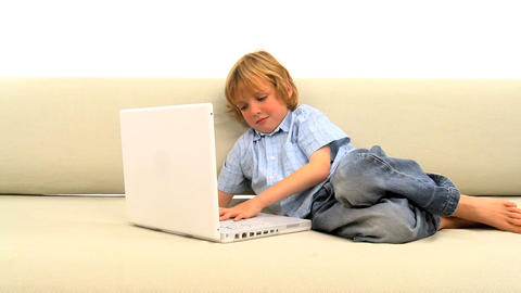 Little boy lying on the sofa and using laptop Stock Video Footage