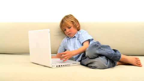 Little boy lying on the sofa and using laptop Footage