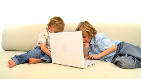 Two little boys playing with laptop on the sofa Footage