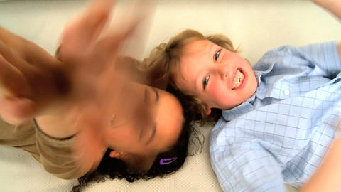 Cute little girl and boy lying down and waving at a camera Stock Video Footage