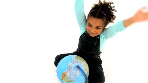 An adorable african american girl sitting on the floor with a globe and waving Footage