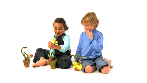 African american girl and blonde boy playing with flowers Stock Video Footage