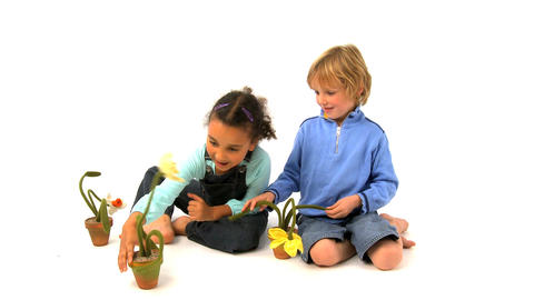 African american girl and blonde boy playing with flowers Footage