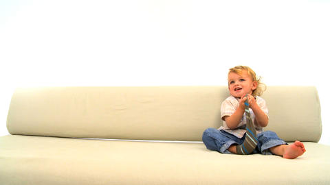 Cute toddler sitting on the sofa and strips socks Stock Video Footage