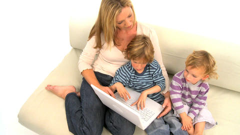 Mother and her cute sons sitting on the sofa and using laptop, motion jib Footage