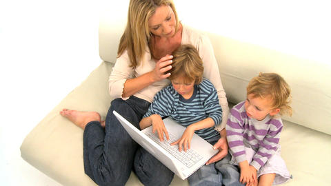 Mother and her cute sons sitting on the sofa and using... Stock Video Footage