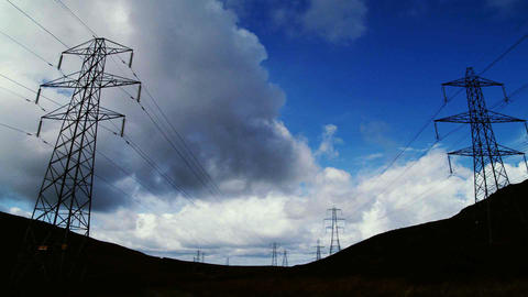 Electricity pylons time-lapse with clouds and blue sky Footage