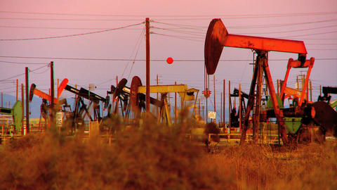 Oil donkeys or pump jacks in perpetual motion at sunset Live Action