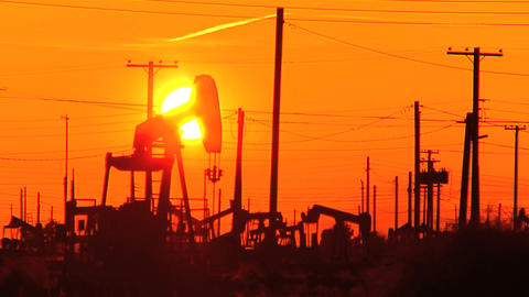 Oil donkeys or pump jacks in perpetual motion at sunset Footage