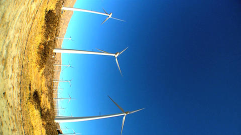 Vertical with fish-eye lens of wind turbines producing clean & renewable energy Footage