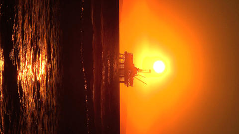 Vertical sunset over oil platform at sea Stock Video Footage