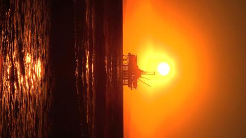 Vertical sunset over oil platform at sea Footage