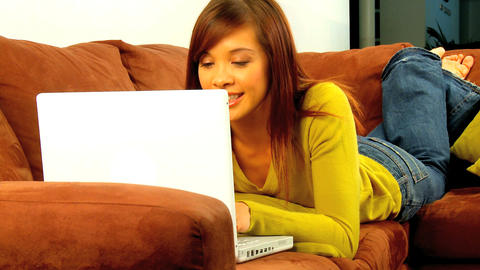 Young western oriental girl relaxing on her sofa & using her laptop computer Footage