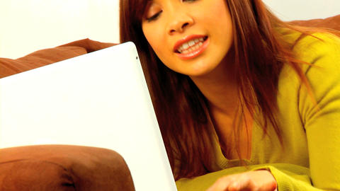 Young western oriental girl relaxing on her sofa & using... Stock Video Footage