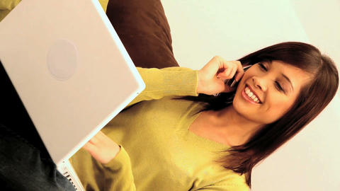 Vertical shot of western oriental girl relaxing at home with her laptop & phone Footage