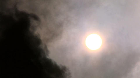 Black smoke being pumped into the atmosphere obscuring the sun Footage
