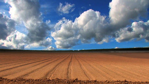 Dramatic time-lapse clouds over a ploughed field Stock Video Footage