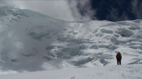 Climber walking towards big ice wall Stock Video Footage