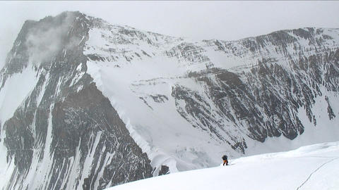 Climber ascending north side up snow slope Stock Video Footage