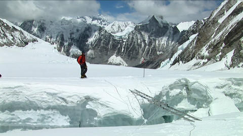 Climber crosses large crevasse above camp one Stock Video Footage