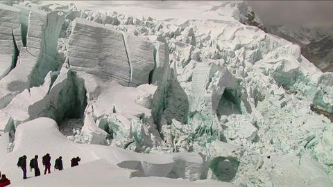 Climbers make their way through large seracs Stock Video Footage