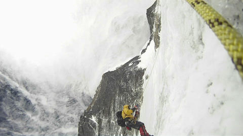 Climber ascends into strong winds Stock Video Footage