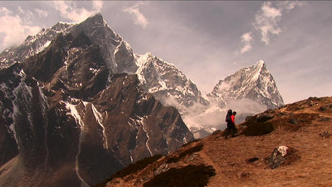 Trekker climbing steep hill with large peak in back Stock Video Footage