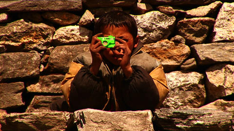 Nepalese boy pretending to take photos with toy Footage