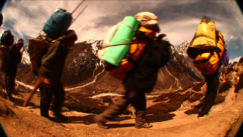 Fish eye shot of porters passing by on trail in Himalayas. Footage