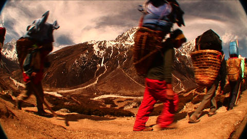 Fish eye shot of porters passing by on trail in Himalayas. Stock Video Footage
