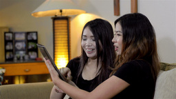 Two Female Friends Looking at Pictures on a Tablet Stock Video Footage