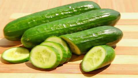 Fresh green cucumber on bamboo cutting board Stock Video Footage
