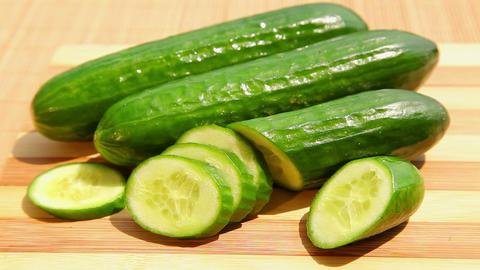 Fresh green cucumber on bamboo cutting board Stock Video Footage