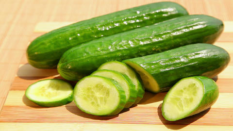 Fresh green cucumber on bamboo cutting board Footage